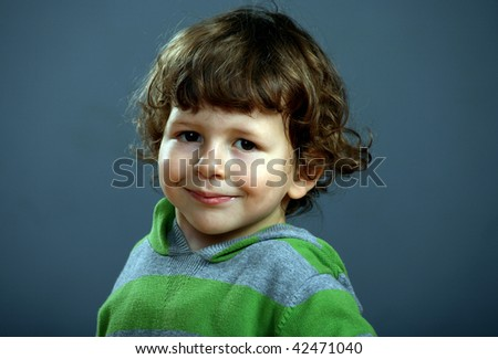 Portarait of a nice little boy with a beautiful curly hair
