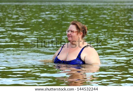 portarit of plump woman bath in river - stock photo