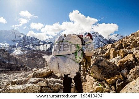 Porter and Sherpa walking with big bag baggage luggage in Himalaya Mountains in Nepal. Khumbu glacier in Everest National Park and people trekking on rocky footpath trail. - stock photo