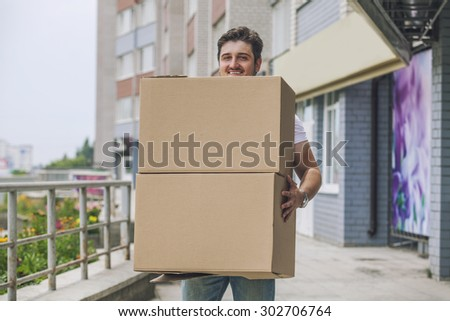 Porter, the man with cardboard boxes in the hands of a strong, delivery to the door. Fast delivery, reliability, deliveryman. - stock photo