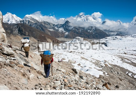 Porter, with Mt. Everest and the himalayas from Renjo mountain pass, Nepal  - stock photo