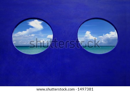 Porthole - View of a calm blue ocean, summer sky.