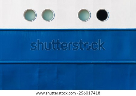 Portholes in white and blue ship's side, one is different, emergency exit - stock photo