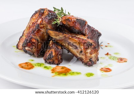 portion hot smoked barbecue ribs on white plate serving in restaurant - stock photo