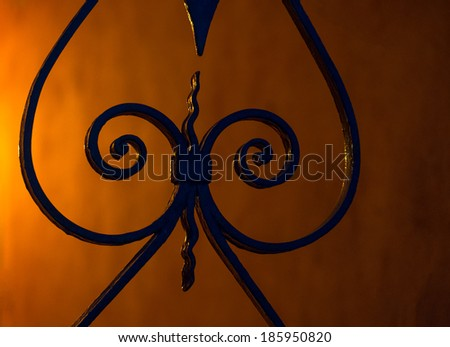 Portion of a wrought iron gate against a wall with glowing light at night. - stock photo
