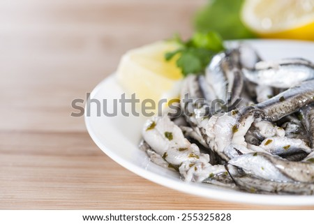Portion of Anchovis with herbs (close-up shot) - stock photo