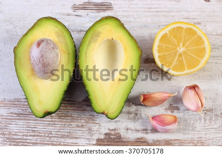 Portion of avocado, clove garlic and lemon, concept of healthy food, nutrition and omega fatty acids, ingredient of avocado paste or guacamole - stock photo