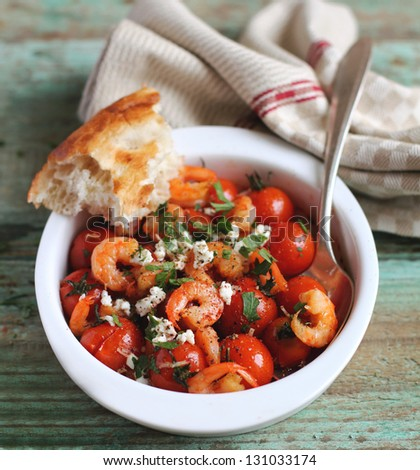 Portion of baked cherry tomatoes and roasted shrimps with greek salted feta cheese and chopped fresh parsley in a baking dish with a slice of bread - stock photo