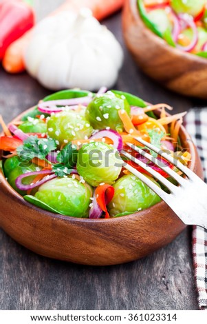 Portion  of Brussels Sprouts with carrot and onions on wooden table  - stock photo