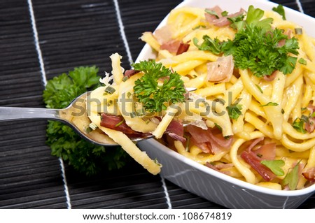 Portion of Cheese Spaetzle in a bowl with portion on fork (on black tablecloth)