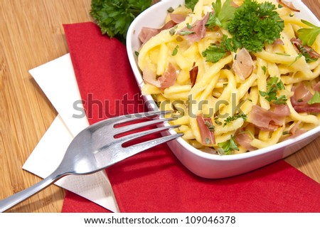 Portion of Cheese Spaetzle with cutlery (macro view) - stock photo