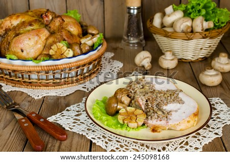 Portion of chicken stuffed with buckwheat with mushrooms on wooden table - stock photo