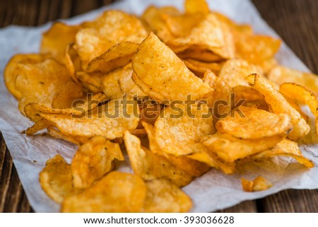 Portion of chilli Potato Chips (close-up shot) on wooden background - stock photo