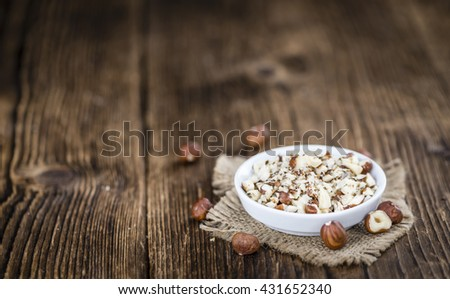 Portion of chopped Hazelnuts on wooden background (close-up shot; selective focus) - stock photo