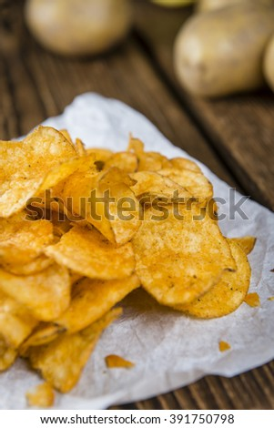 Portion of crispy Potato Chips (selective focus) on wooden background