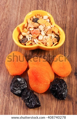 Portion of dried fruits and muesli in bowl, concept of healthy nutrition and increase metabolism, ingredients with dietary fiber - stock photo