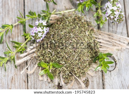 Portion of dried Winter Savory on wooden background