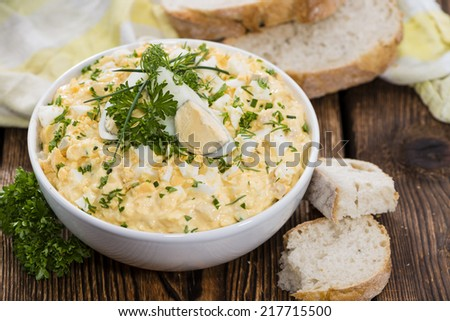Portion of Egg Salad (fresh homemade with herbs) on wooden background - stock photo