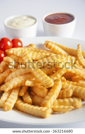 Portion of French fries (Crinkle-cut) deep fried, served on a white plate next to white bowls with mayonnaise and ketchup. - stock photo