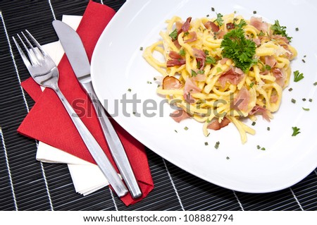 Portion of fresh Cheese Spaetzle decorated with fresh herbs on black tablecloth
