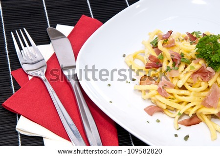 Portion of fresh Cheese Spaetzle decorated with fresh herbs on black tablecloth - stock photo