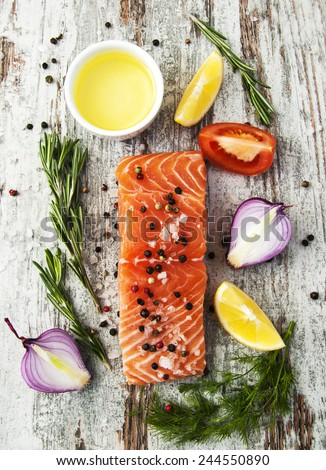 portion of fresh salmon fillet with aromatic herbs, spices and vegetables - stock photo