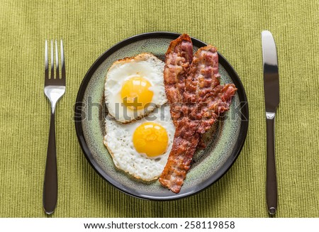 Portion of fried eggs with bacon - stock photo