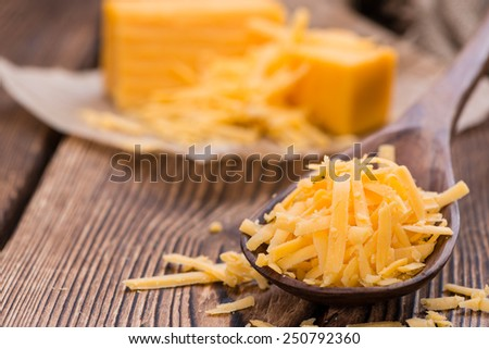 Portion of grated Cheddar Cheese on rustic wooden background - stock photo