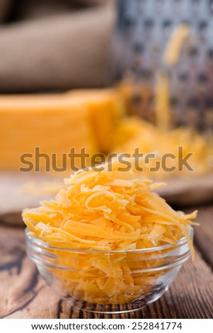Portion of grated Cheddar Cheese on rustic wooden background