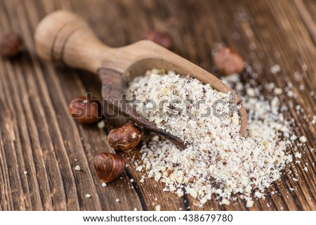 Portion of grounded Hazelnuts (selective focus; close-up shot) on wooden background - stock photo
