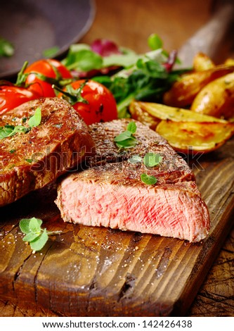 Portion of healthy lean grilled beef steak sliced through to reveal the rare interior served on a wooden board with roast vegetables - stock photo