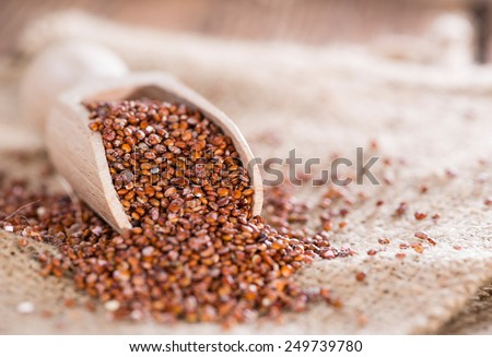 Portion of healthy red Quinoa on wooden background - stock photo