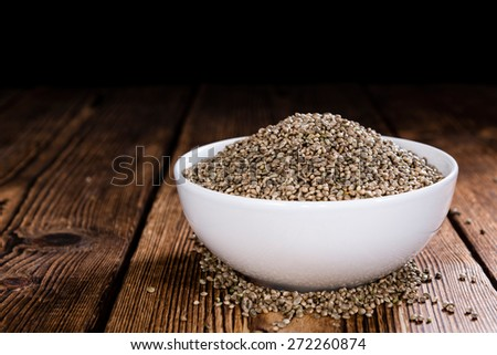 Portion of Hemp Seeds (close-up shot) on an old wooden table - stock photo