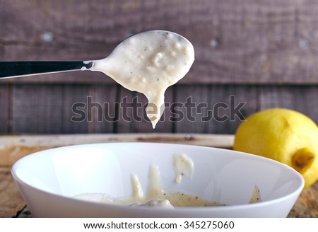 Portion of homemade Aioli dip - garlic mayonnaise on wooden background. Fresh aioli drains from spoon to white plate. - stock photo
