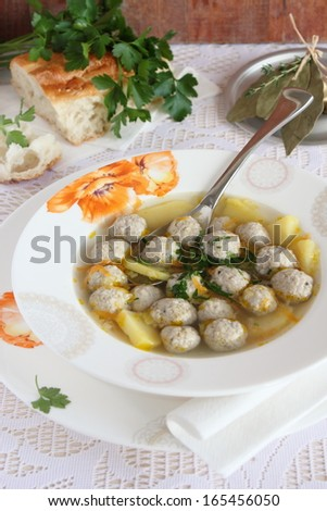 Portion of homemade soup with meatballs in the white plate.