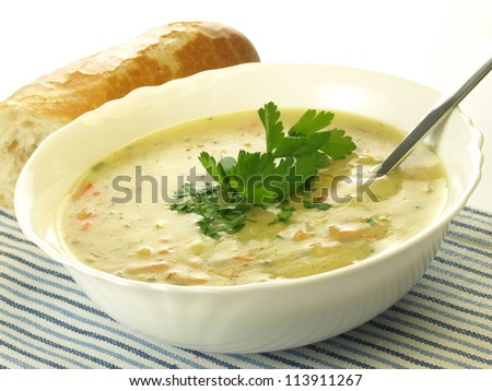 Portion of homemade vegetable soup with roll, isolated