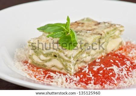 Portion of lasagna garnished with salad greens - stock photo