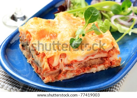 Portion of lasagna garnished with salad greens  - stock photo