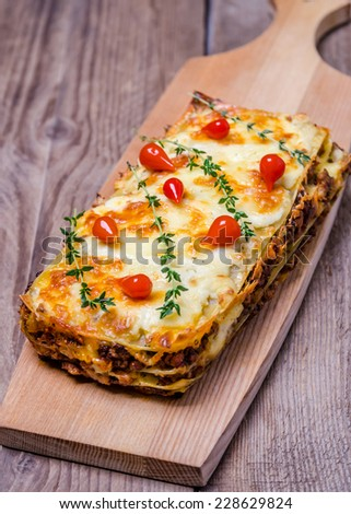 Portion of lasagna on the wooden table - stock photo