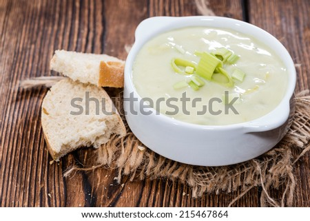 Portion of Leek Soup in a small bowl on dark wooden background