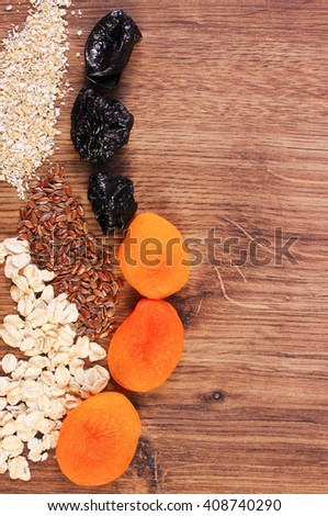 Portion of linseed, rye flakes, oat bran and dried fruits, concept of healthy nutrition and increase metabolism, ingredients with dietary fiber, copy space for text - stock photo