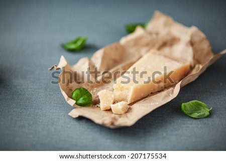 Portion of mature Italian Parmesan cheese with a traditional hard granular texture with scattered fresh basil on crinmpled brown paper, on a grey cloth with copyspace - stock photo