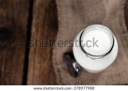Portion of Milk on wooden background (close-up shot) - stock photo
