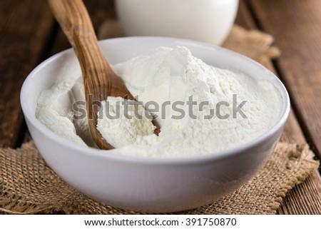 Portion of Milk Powder (selective focus) on an old wooden table - stock photo
