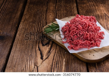 Portion of Minced Meat on an old wooden table (close-up shot) - stock photo
