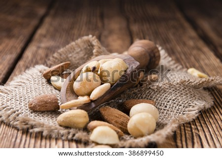 Portion of mixed nuts (roasted and salted) on an old wooden table (selective focus)