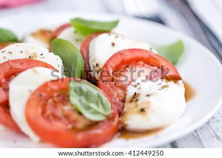 Portion of Mozarella with Tomatoes and Balsamico dressing (selective focus; close-up shot)