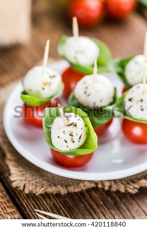 Portion of Mozzarella with Tomatoes on an old wooden table (selective focus)