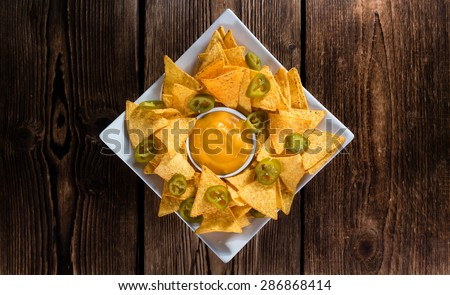 Portion of Nachos (with Cheese Dip) on an old wooden table - stock photo