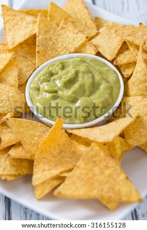 Portion of Nachos (with Guacamole) on wooden background